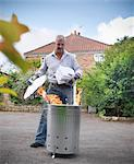 Man burning papers in garbage can Stock Photo - Premium Royalty-Free, Artist: Photocuisine, Code: 649-06400996