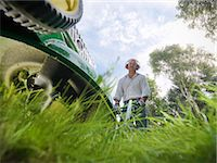 Low angle view of man mowing lawn Stock Photo - Premium Royalty-Freenull, Code: 649-06400999