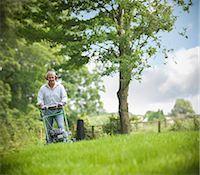 Man wearing headphones and mowing lawn Stock Photo - Premium Royalty-Freenull, Code: 649-06401000