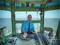 ships at sea - Captain steering tugboat in wheelhouse Stock Photo - Premium Royalty-Freenull, Code: 649-06401021