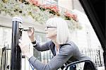 Woman charging electric car on street Stock Photo - Premium Royalty-Freenull, Code: 649-06401083