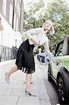 Woman opening car door on city street Stock Photo - Premium Royalty-Freenull, Code: 649-06401101