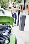 Woman charging electric car on street Stock Photo - Premium Royalty-Free, Artist: Blend Images, Code: 649-06401107
