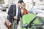 Couple charging electric car on street Stock Photo - Premium Royalty-Freenull, Code: 649-06401110