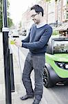 Man charging electric car on street Stock Photo - Premium Royalty-Freenull, Code: 649-06401123