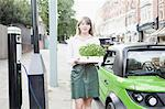Woman carrying flowerbox on city street Stock Photo - Premium Royalty-Freenull, Code: 649-06401125