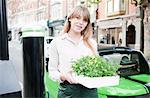 Woman carrying flowerbox on city street Stock Photo - Premium Royalty-Freenull, Code: 649-06401126