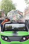 Couple balancing umbrella on car roof Stock Photo - Premium Royalty-Free, Artist: Blend Images, Code: 649-06401137