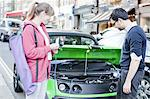 Couple charging electric car on street Stock Photo - Premium Royalty-Freenull, Code: 649-06401141