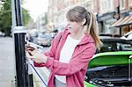Woman charging electric car on street Stock Photo - Premium Royalty-Freenull, Code: 649-06401144