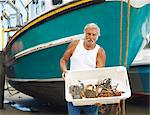 Fisherman holding catch on boat Stock Photo - Premium Royalty-Free, Artist: David Papazian, Code: 649-06401176