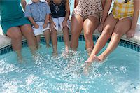 Family dangling feet in swimming pool Stock Photo - Premium Royalty-Freenull, Code: 649-06401401