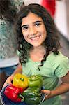Smiling girl holding bowl of peppers Stock Photo - Premium Royalty-Free, Artist: Andrew Kolb, Code: 649-06401419