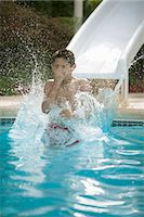 preteen swim - Boy on water slide splashing into pool Stock Photo - Premium Royalty-Freenull, Code: 649-06401431