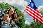 Teenage girl leaning out of car window holding american flag Stock Photo - Premium Royalty-Free, Artist: Yvonne Duivenvoorden, Code: 614-06402502