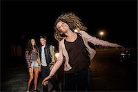 person walking on parking lot - Three friends in parking lot at night Stock Photo - Premium Royalty-Freenull, Code: 614-06402553