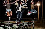 Four friends jumping over bleachers at night Stock Photo - Premium Royalty-Free, Artist: GreatStock, Code: 614-06402601