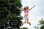 Girl on trampoline Stock Photo - Premium Royalty-Free, Artist: Ikon Images, Code: 614-06402643