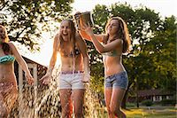 Girl pouring bucket of water over friend's head Stock Photo - Premium Royalty-Freenull, Code: 614-06402688