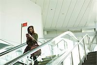 people on mall - Young woman on escalator using smartphone Stock Photo - Premium Royalty-Freenull, Code: 614-06402753