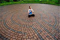 pattern (man made design) - Woman meditating in paving stone circles Stock Photo - Premium Royalty-Freenull, Code: 614-06402798