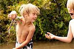 Boy holding frog up whilst friend looks on in amazement Stock Photo - Premium Royalty-Free, Artist: Cusp and Flirt, Code: 614-06402886