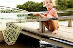 Girl on jetty with frog in fishing net Stock Photo - Premium Royalty-Free, Artist: Cusp and Flirt, Code: 614-06402889