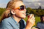 Teenage girl in sunglasses drinking from juice carton Stock Photo - Premium Royalty-Free, Artist: Blend Images, Code: 614-06403096