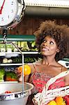 African American woman weighing bell peppers on scale at supermarket Stock Photo - Premium Royalty-Free, Artist: Blend Images, Code: 693-06403163