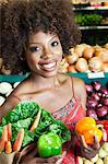 African American woman holding bell peppers and vegetables at supermarket Stock Photo - Premium Royalty-Free, Artist: AWL Images, Code: 693-06403166