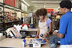 Portrait of an African American female store clerk standing at checkout counter scanning item serving male customer Stock Photo - Premium Royalty-Free, Artist: Blend Images, Code: 693-06403175