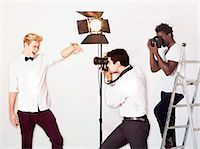 Paparazzi taking photographs of male actor over white background Stock Photo - Premium Royalty-Freenull, Code: 693-06403191
