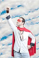 Young man in superhero costume with hand raised against cloudy sky Stock Photo - Premium Royalty-Freenull, Code: 693-06403199