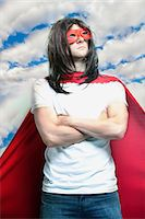 Young man in super hero costume with arms crossed against cloudy sky Stock Photo - Premium Royalty-Freenull, Code: 693-06403206