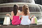 Back view of two young female friends with shopping bags sitting by water fountain Stock Photo - Premium Royalty-Free, Artist: Blend Images, Code: 693-06403239