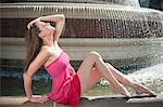 Side view of beautiful young woman in pink dress sitting by water fountain Stock Photo - Premium Royalty-Free, Artist: Robert Harding Images, Code: 693-06403241