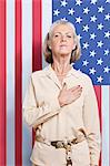 Portrait of senior woman with hand over heart against American flag Stock Photo - Premium Royalty-Free, Artist: Siephoto, Code: 693-06403439