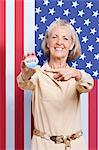 Portrait of senior woman pointing at election badge against American flag Stock Photo - Premium Royalty-Free, Artist: Raymond Forbes, Code: 693-06403442