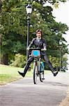 Portrait of young businessman riding bicycle with legs kicked out Stock Photo - Premium Royalty-Free, Artist: CulturaRM, Code: 693-06403491
