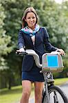 Young businesswoman with bicycle standing at park Stock Photo - Premium Royalty-Free, Artist: Westend61, Code: 693-06403499