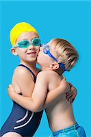Young siblings in swimwear embracing and kissing over blue background Stock Photo - Premium Royalty-Freenull, Code: 693-06403572