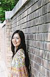 Portrait of a smiling Japanese woman leaning against a brick wall Stock Photo - Premium Rights-Managed, Artist: Aflo Relax, Code: 859-06404898