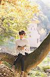 Japanese woman in a white cardigan reading a book sitting on a tree Stock Photo - Premium Rights-Managed, Artist: Aflo Relax, Code: 859-06404985