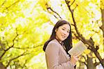 Japanese woman with long hair looking at camera while holding a book with yellow leaves in the background Stock Photo - Premium Rights-Managed, Artist: Aflo Relax, Code: 859-06404991