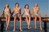 Young friends sitting in a row on pier Stock Photo - Premium Royalty-Freenull, Code: 618-06405669