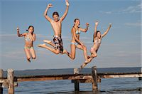 preteen bathing suit - Young friends jumping from pier into sea Stock Photo - Premium Royalty-Fr