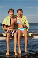 Young teenage couple sitting on pier, smiling, portrait Stock Photo - Premium Royalty-Freenull, Code: 618-06405672