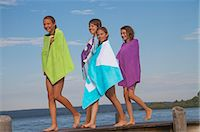 preteen girl - Four young friends wrapped in towels walking on pier Stock Photo - Premium Royalty-Freenull, Code: 618-06405675