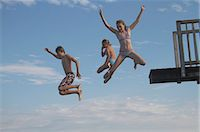 preteen bathing suit - Young friends jumping into sea from pier Stock Photo - Premium Royalty-Freenull, Code: 618-06405679