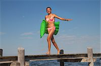 Teenage girl walking along pier holding airbed Stock Photo - Premium Royalty-Freenull, Code: 618-06405681